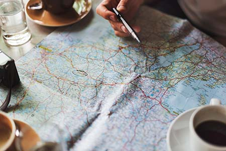Person studying a map to relate to the idea of a brief as a map for your transcreator