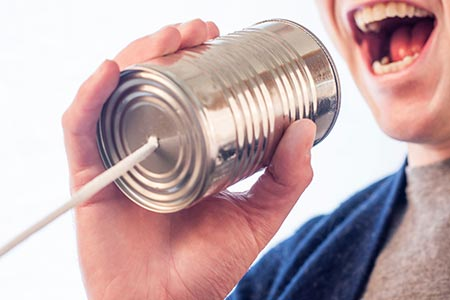 Man speaking into a tin can with string attached to it, as an allegory for the contact us page in website translations.