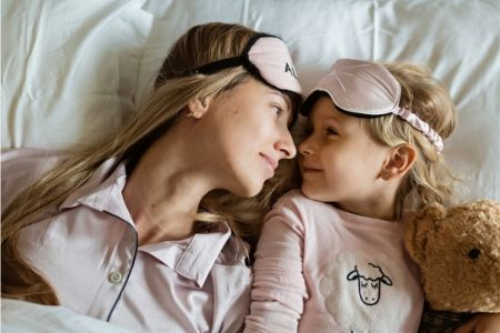 A mother and daughter in bed during quarantine.